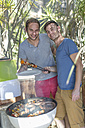 Happy gay couple preparing food on barbecue grill - ZEF004271