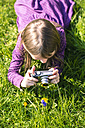 Little girl lying on meadow photographing a flower - SARF001791