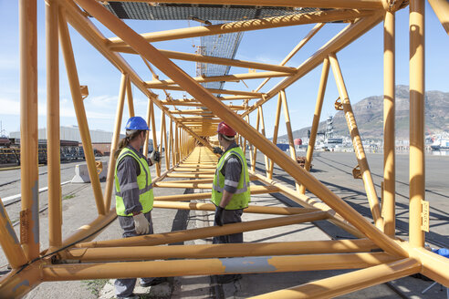 Two workers at port with steel girder construction - ZEF005707