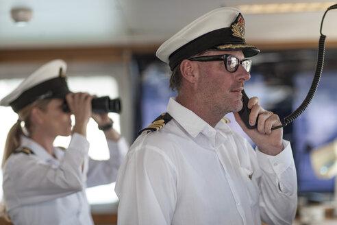 Ship captain on bridge talking on radio - ZEF005491