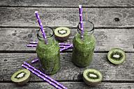 Green smoothie with kiwi, banana and mache, drinking straws, wood - SARF001750