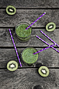 Green smoothie with kiwi, banana and mache, drinking straws, wood - SARF001752