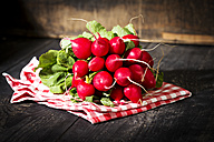 Bunch of red radish on kitchen towel and wood - MAEF010311