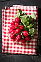 Bunch of red radish on kitchen towel and wood - MAEF010312