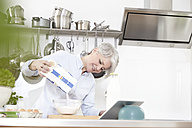 Mature woman in kitchen pouring flour in bowl - FMKF001471
