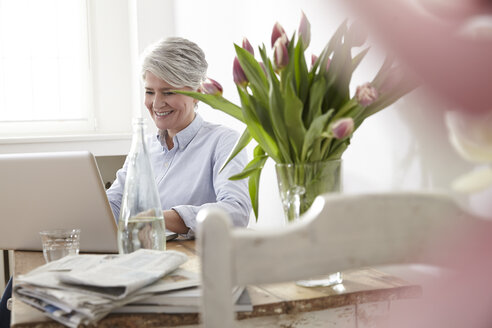 Mature woman sitting at table using laptop - FMKF001478