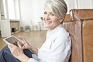Mature woman sitting on floor using digital tablet - FMKF001486