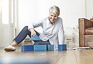 Mature woman sitting on floor with building bricks - FMKF001490