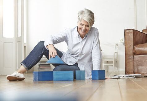 Mature woman sitting on floor with building bricks - FMKF001490