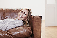Smiling blond young woman lying on couch - FMKF001505