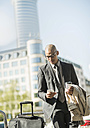 Businessman with suitcase looking on smartphone - UUF004010