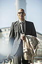 Businessman with suitcase and coffee to go - UUF004012