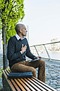 Man sitting on bench with digital tablet - UUF004014
