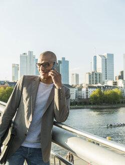 Germany, Frankfurt, businessman on bridge talking on smartphone - UUF004036