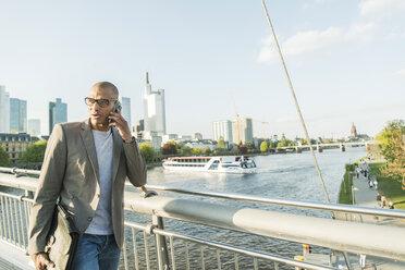 Germany, Frankfurt, businessman on bridge talking on smartphone - UUF004038
