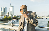 Germany, Frankfurt, businessman on bridge talking on smartphone - UUF004039