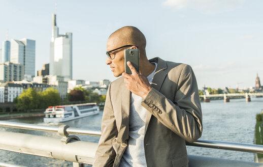 Germany, Frankfurt, businessman on bridge talking on smartphone - UUF004039