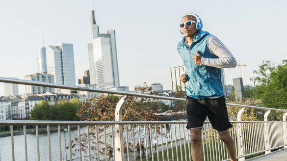 Germany, Frankfurt, man wearing headphones jogging on bridge - UUF004048