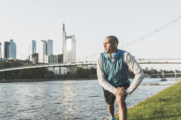 Germany, Frankfurt, man stretching by the riverside - UUF004054