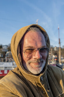 Portrait of smiling mature man wearing sunglasses and hooded jacket - EGBF000034