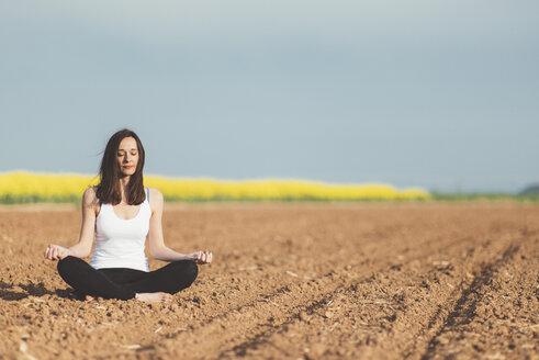 Woman meditating on a field - JPF000040