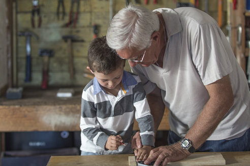 Grandfather and grandson working with wood in a garage - ZEF004602