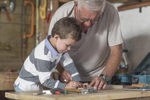 Grandfather and grandson working with wood in a garage - ZEF004607