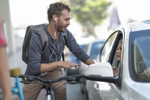 Man on bicycle talking to woman in car - ZEF004897