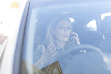 Frustrated woman in car stuck in traffic jam - ZEF004678