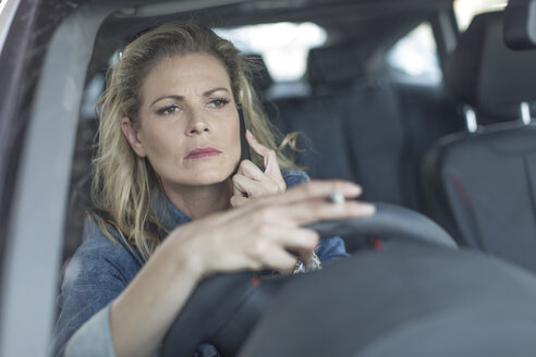 Serious woman in car on cell phone - ZEF004681