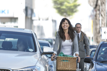 Smiling woman on bicycle in traffic jam - ZEF004683