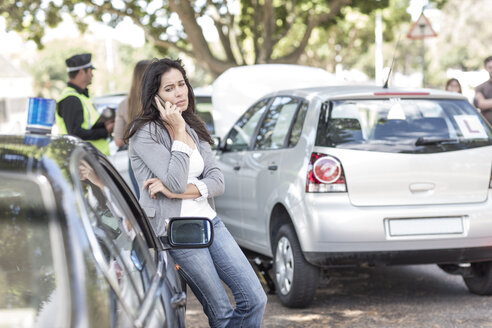 Woman on cell phone at car accident scene - ZEF004761