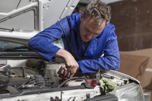 Man working on car in home garage - ZEF004815