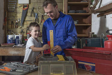 Father and son working in home garage - ZEF004819