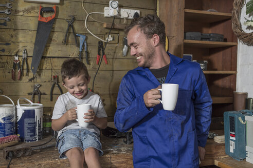 Father and son working in home garage having coffee break - ZEF004821