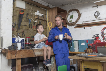 Father and son working in home garage having lunch break - ZEF004908