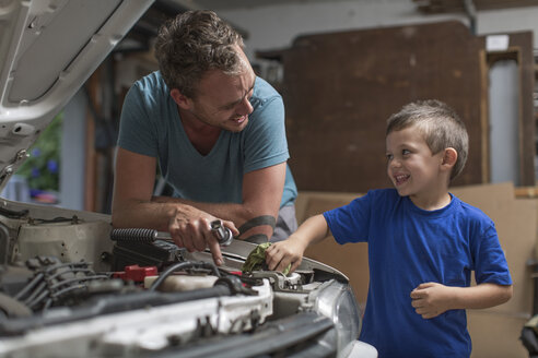 Son helping father in home garage working on car - ZEF004825