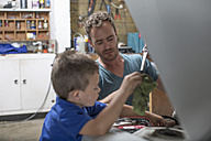 Son helping father in home garage working on car - ZEF004878