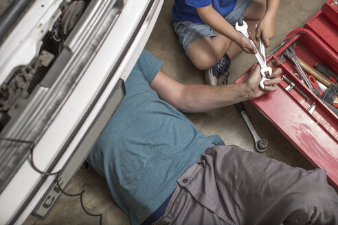 Son helping father in home garage working on car - ZEF004829