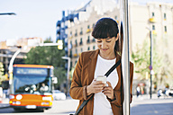 Spain, Barcelona, businesswoman with smartphone waiting at the bus stop - EBSF000590