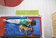 Dog lying on bed with boy using digital tablet - PDF000927