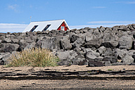 Iceland, Stokkseyri, house hidden behind stone wall - KEBF000166