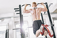 Young man exercising chin-ups on power rack in gym - MADF000220