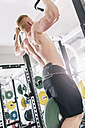 Young man exercising chin-ups on power rack in gym - MADF000222