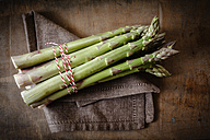 Bunch of green asparagus on cloth and wood - EVGF001673