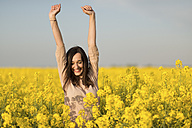 Happy woman in a blossoming rape field - JPF000041