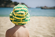 Spain, Mallorca, Porto Christo, back view of little boy sitting on the beach wearing summer hat - MFF001587