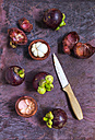 Whole and opened mangosteens and a kitchen knife - KNTF000021