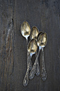 Five old silver spoons on dark wood - CRF002686