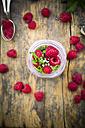 Raspberries, chia, milk, kiwi, hemp seed and mint in a glass - LVF003321